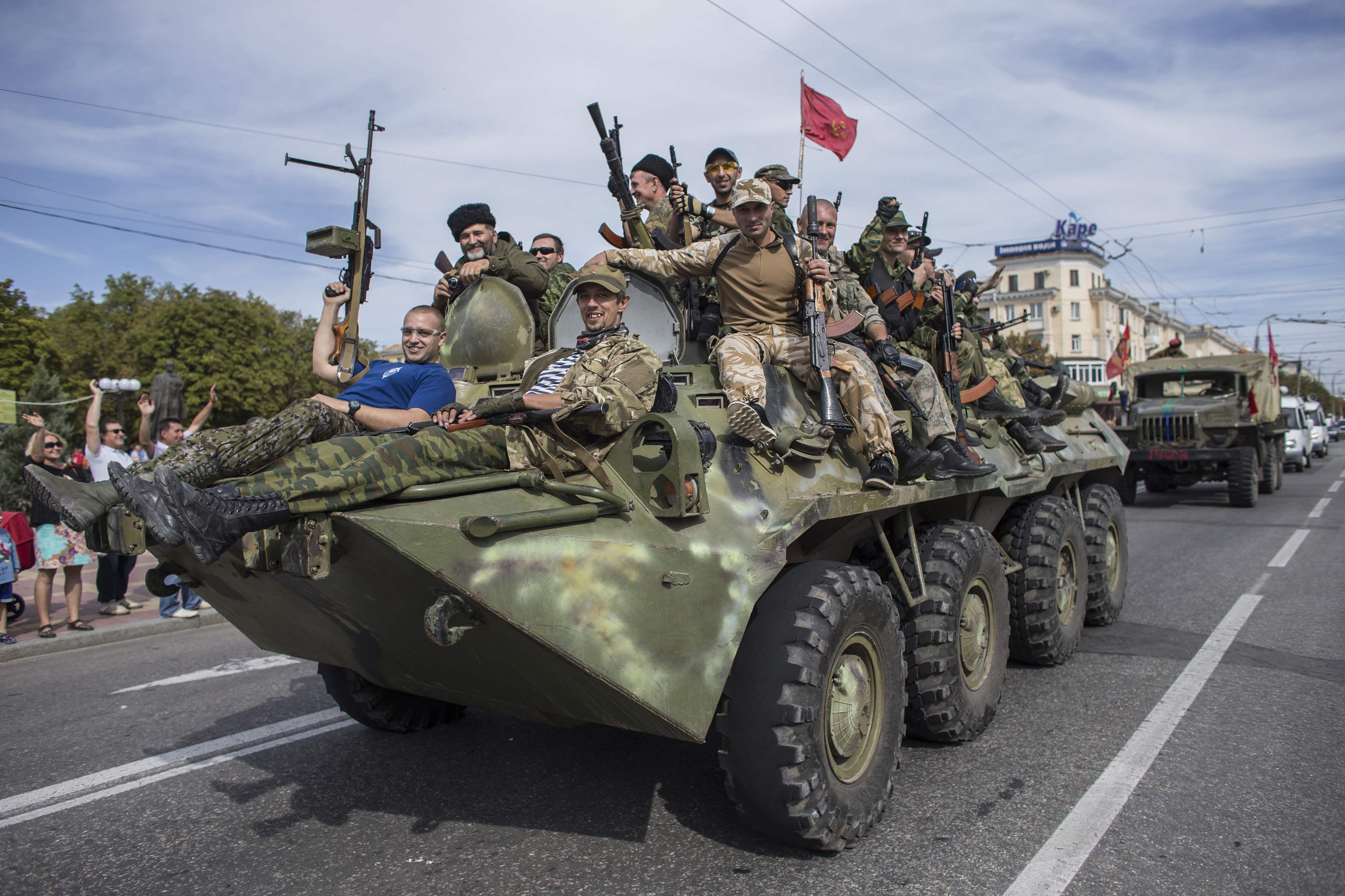 Pro-Russian rebels ride on an APC during a parade in Luhanks, eastern Ukraine