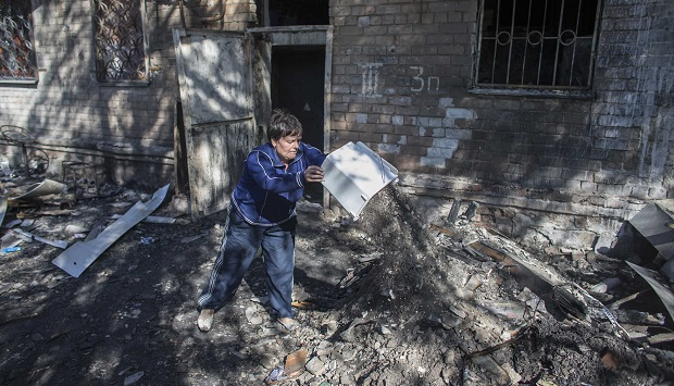 Woman cleans up debris outside a building that was recently shelled in Donetsk, eastern Ukraine